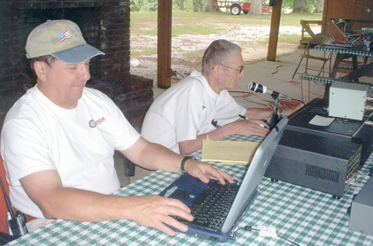 Radio operator George, KJ2V makes a contact with a distant station while Harry, K3HK logs the information into the computer.