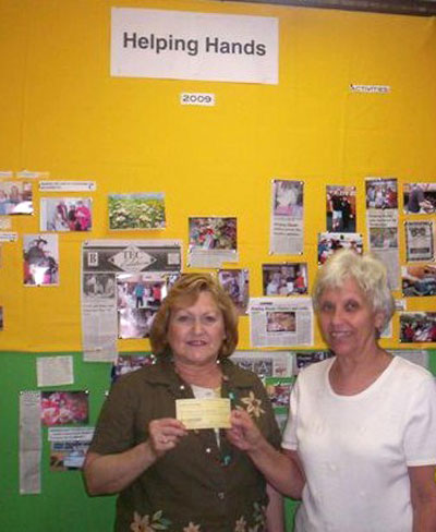 Carolyn O'Neal of Neighbors & Newcomers present the club's donation to Carol Beyer, President of Helping Hands.