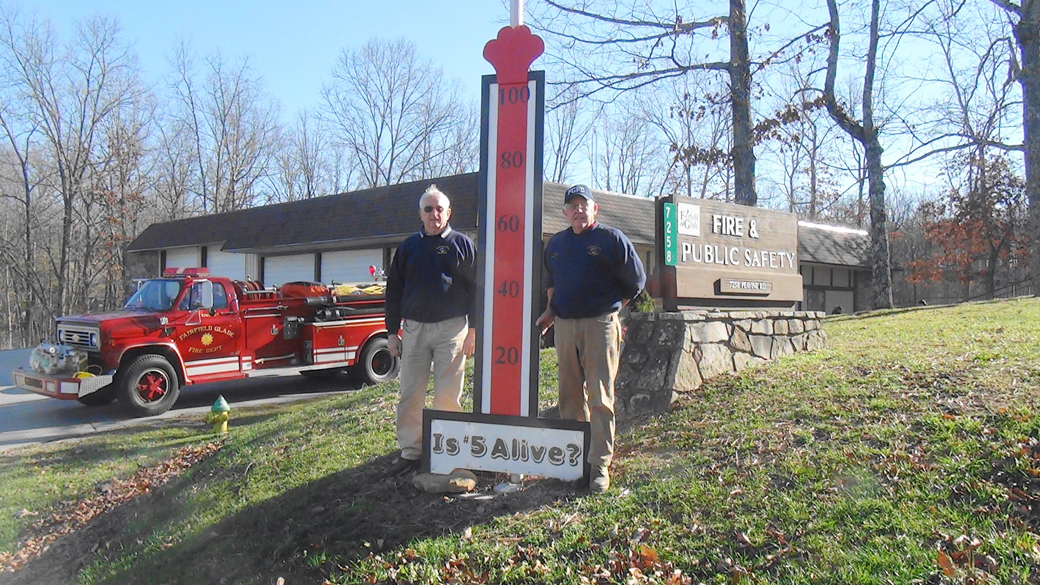 Glade Records Officer Jim Etzel, left, and Fire Chief Howard Robb pose next to the donation tracker displayed on Peavine Road.