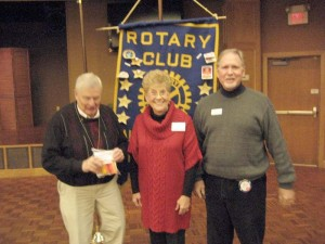 Fairfield Glade Rotary Vice-president James Thompson welcomes new Rotarian Robert (Bobby) Smith as his Smith's wife Sharon adds his pin.