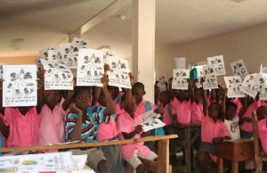 Above, Haiti school children learn about safe water and hold up the diagrams for providing bio sand water filters.