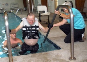 Wayne Howell (center) strains his upper arms to lift his paralyzed leg up a step at tthe pool in the Cumberland Medical Center Wellness Complex at Fairfield Glade as part of his efforts at rehabilitation. He is encouraged by his trainer, Wayne Henline (left, in the pool), and his wife, Irene (right).
