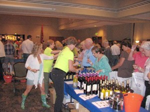 Cathy Fine (foreground, yellow shirt) serves up some samples to patrons at the recent Wine on the Plateau event hosted by the Fairfield Glade Rotary.