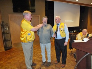 Pictured (L-R) are Lions Club President Marty Smith placing pin on newest member, Ed Carter. 1st Vice District Governor Mel Tryon performed the induction.