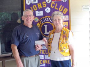 Fire Chief Howard Robb accepts a $500.00 check from King Lion Carol Pontius.